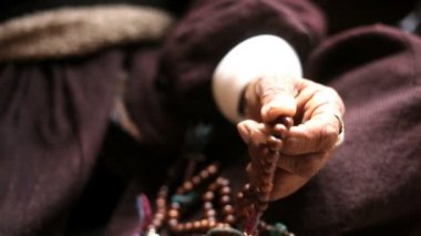Hand of elderly woman using prayer beads — Stock Video
