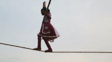 Young female tightrope walker on the beach — Stock Video