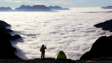 Hiker with binoculars above the clouds — Stok video
