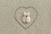 Pebbles shapes lovers on the beach — Stock Photo