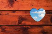 Heart shaped hole with blue sky and white clouds in a brown wooden wall. — Stock Photo