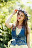 Young woman touching flower wreath on her head — Stock Photo