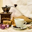 Coffee mill with burlap sack of roasted beans and white cup of prepared espresso on the white knitted linen table-cloth — Stock Photo #59209713