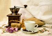 Coffee mill with burlap sack of roasted beans and white cup of prepared espresso on the white knitted linen table-cloth — Stock Photo