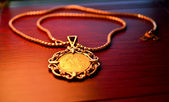 One way hoe to use investment gold coin. Gold sovereign coin as woman jewelry pendant on a chain — Stock Photo