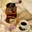 Coffee mill with burlap sack of roasted beans and white cup of coffee — Stock Photo #61002993