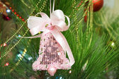 Pink decoration, which has bell shape, on Christmas tree — Stock Photo