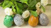 Quatro ovos de Páscoa pintado à mão e flores. — Fotografia Stock