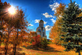 Church in the autumn forest on a background beautiful sky — Stock Photo