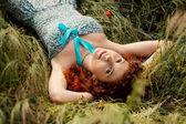 Beautiful redhead woman lying on grass — Stockfoto