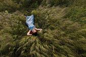Beautiful woman sleeping on tall grass — Stock Photo
