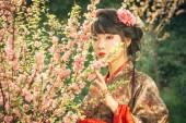 Beautiful asian woman in sakura blossom — Stock Photo