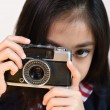 Little girl shooting with a vintage camera — Stock Photo #62214189