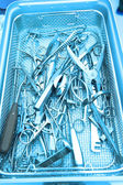 Detail shot of steralized surgery instruments with a hand grabbing a tool — Stock Photo