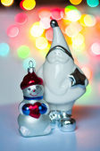 Figurine of Santa Claus and Snowman in the background of multi-colored lights — Stock Photo