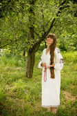 Young girl in the Ukrainian embroidered shirt, standing barefoot — Stock Photo