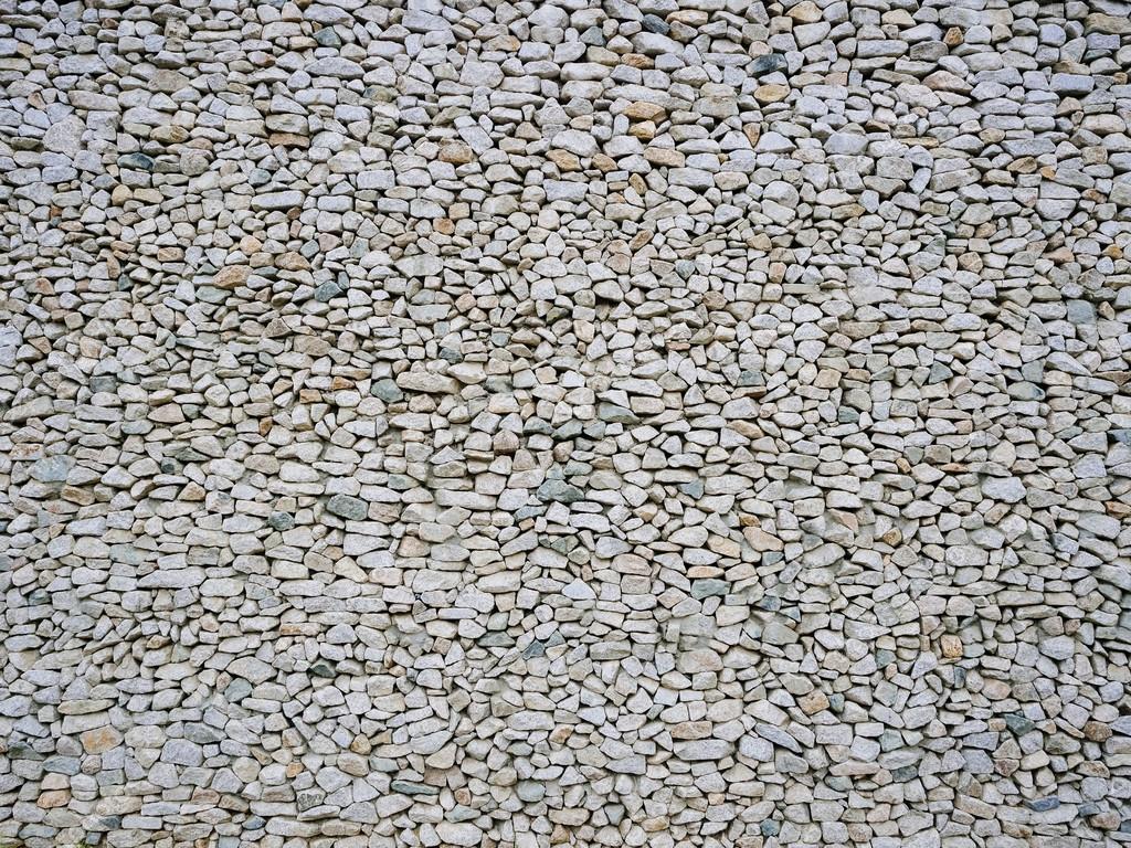 Ciottoli di ghiaia di grana Wall Texture sfondo — Foto Stock ...