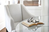 Living room armchair with book and eyeglasses — Stock Photo
