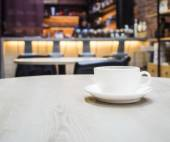 Coffee cup on table with blurred counter Bar Cafe restaurant backgroud — Stock Photo