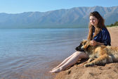 Girl with a dog is on the shore of Lake Baikal — Stock Photo