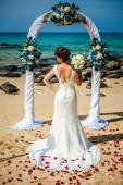Beautiful Happy Girl in wedding dress in the background of wedding arches on the seafront — Stockfoto