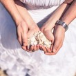 Man and woman holding sand and shells coral with a wedding ring on the beach — Stock Photo #61753087