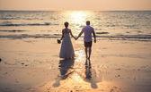 Milující pár na tropické pláži proti moři pozadí oceán západu slunce — Stock fotografie