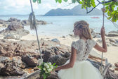 Beautiful girl in a wedding dress on the swing in the background of the Andaman sea Similan Island — Stock Photo