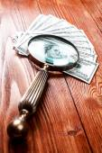 Dollars and magnifying glass — Stock Photo