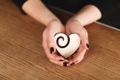 Hands holding wooden heart — Stock Photo