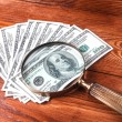 Dollars and magnifying glass — Stock Photo #71107455