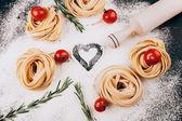 Pasta, tomatoes, rosemary on black — Stock Photo