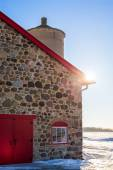 Old Stone Barn with Bright Red Door and Sunflare — Stock Photo