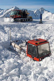 One snowcat is almost covered by snow. Another snowcat is bringing people uphill. — Stock Photo