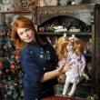 Girl with a doll in Christmas — Stock Photo #64642293