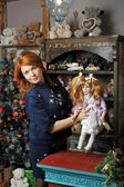 Girl with a doll in Christmas — Stock Photo
