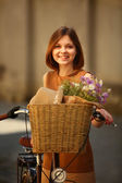 Pretty young woman with bicycle in the park — Stock Photo