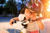 Little girl with bicycle in summer park against sunset — Stock Photo