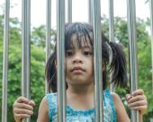 Girls in cages, stainless steel made a sad face. — Stock Photo