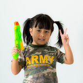 Girl holding two fingers and gun in military uniform on white background — Stock Photo