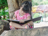 Outdoor portrait of a cute little girl writing a book — Stock Photo