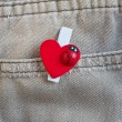 Red heart clothes peg on jeans — Stock Photo #64340261