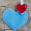 Red heart clothes peg and blue heart on jeans background — Stock Photo #64340285