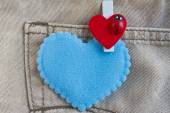 Red heart clothes peg and blue heart on jeans background — Stock Photo