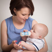 Young Mother Feeding Her Baby Boy With A Milk Bottle — Stock Photo