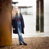 Blond Teenage Girl Leaning Against a Rusty Pier Support — Stock Photo