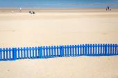 Long Blue Fence On The Beach. — Stock Photo