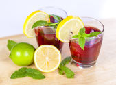 Two glasses of red fruit juice with lemon and lime — Zdjęcie stockowe