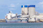 Cargo ship unloading at a cement plant — Stock Photo