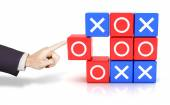 Hand pushing a circle to win the tic tac toe game — Foto de Stock